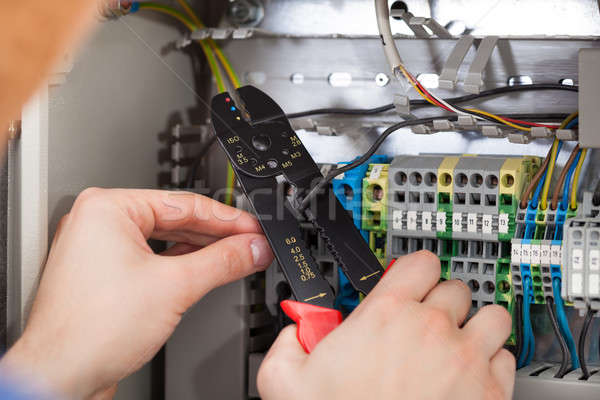 Technician Cutting Cable With Fusebox In Background Stock photo © AndreyPopov