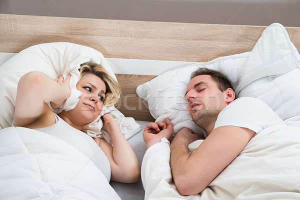 Woman Covering Ears While Man Snoring Stock photo © AndreyPopov