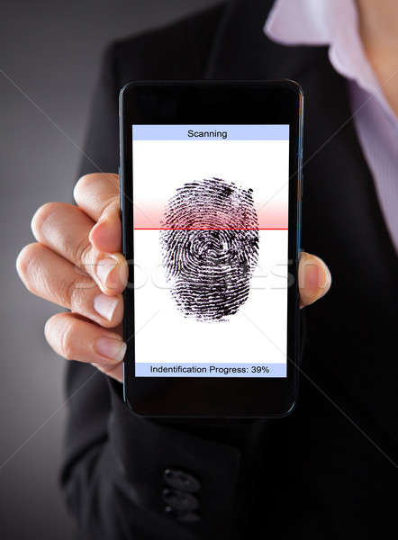 Businessperson With Cellphone Scanning A Fingerprint  Stock photo © AndreyPopov