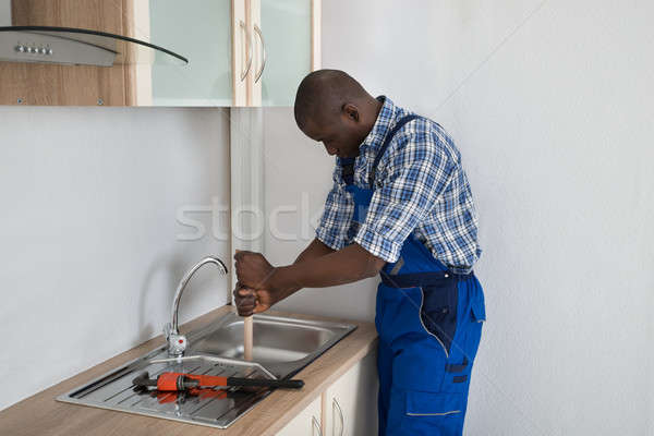 Plumber Pressing Plunger In Sink Stock photo © AndreyPopov