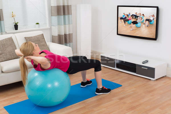 Mulher fitness bola assistindo programa Foto stock © AndreyPopov