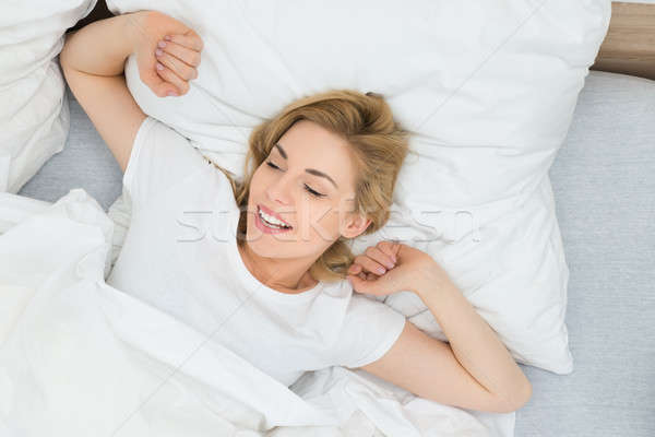 Woman Stretching Arms In Bed Stock photo © AndreyPopov