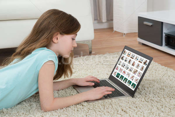 Girl Looking At Pictures On Laptop Stock photo © AndreyPopov