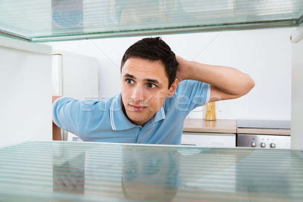 Stock photo: Shocked Man Looking Into Empty Refrigerator
