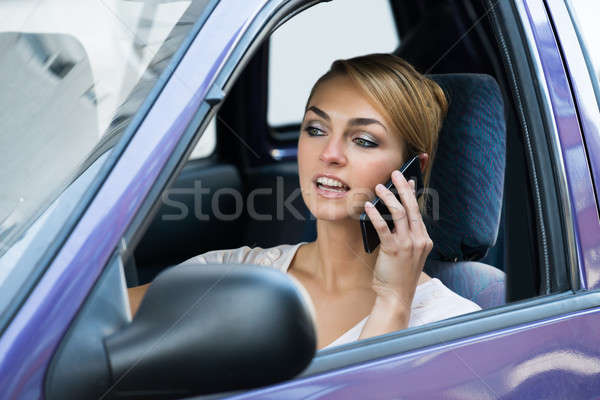 Woman Using Mobile Phone While Driving Car Stock photo © AndreyPopov