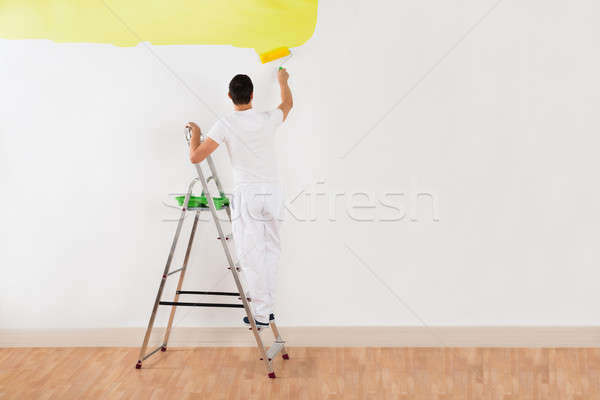 Stock photo: Man Painting Wall With Yellow Paint Roller