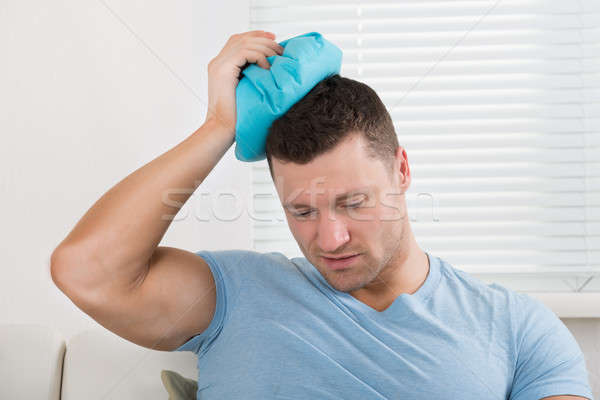 Upset Man Holding Hot Water Bottle On Head Stock photo © AndreyPopov