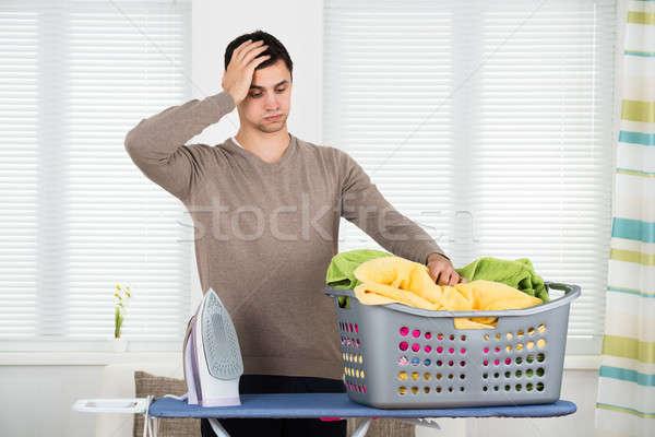 Cansado hombre mirando cesta de la ropa bordo Foto stock © AndreyPopov