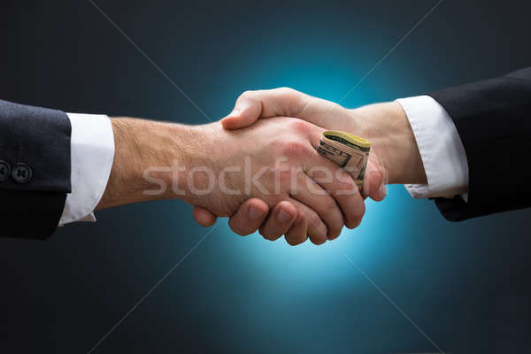 Businessman Shaking Hands While Giving Bribe To Partner Stock photo © AndreyPopov