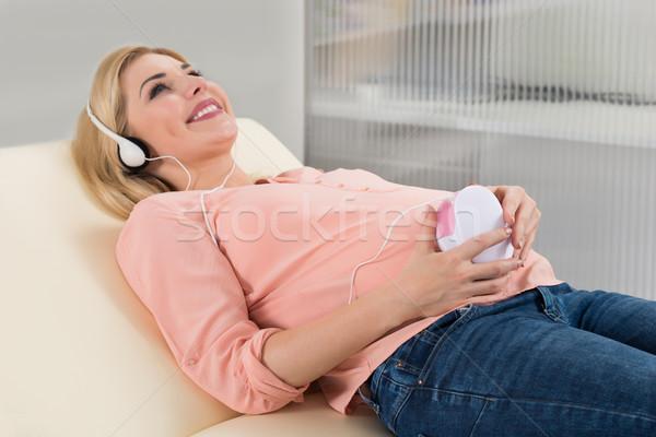 Mulher grávida escuta bebê batimento cardíaco fones de ouvido feliz Foto stock © AndreyPopov