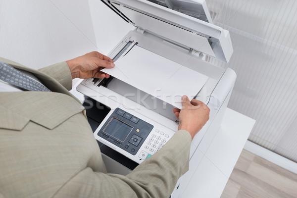 Businessman Keeping Paper On Photocopy Machine Stock photo © AndreyPopov