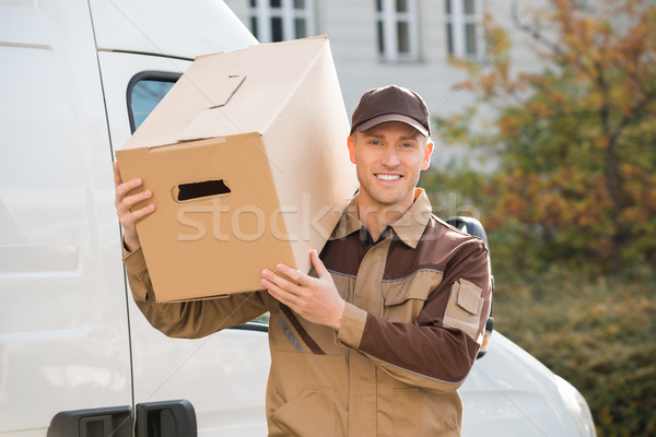 Delivery Man Carrying Cardboard Box On Shoulder Stock photo © AndreyPopov