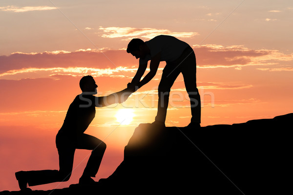 Man Assisting Male Friend In Climbing Rock During Sunset Stock photo © AndreyPopov