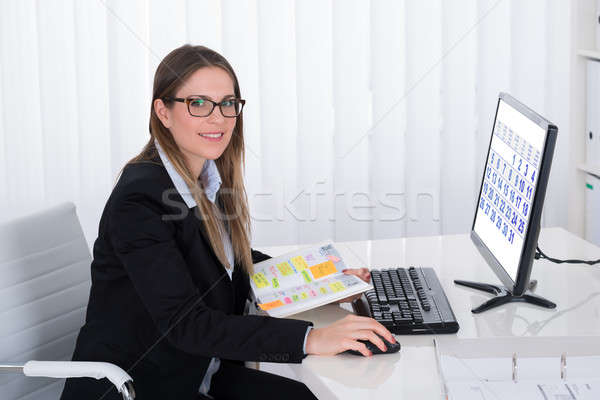 Businesswoman With Diary Looking At Computer Stock photo © AndreyPopov