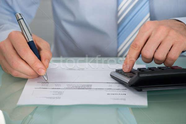 Businessman Calculating Invoice With Calculator Stock photo © AndreyPopov