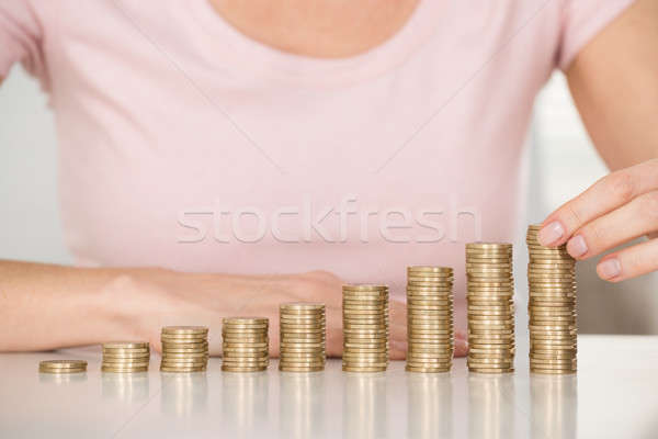 Woman Stacking Coins At Desk Stock photo © AndreyPopov