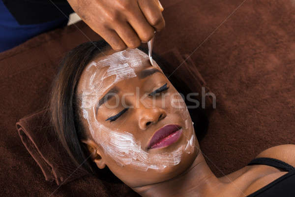 African Woman Applying Facial Mask In Spa Stock photo © AndreyPopov