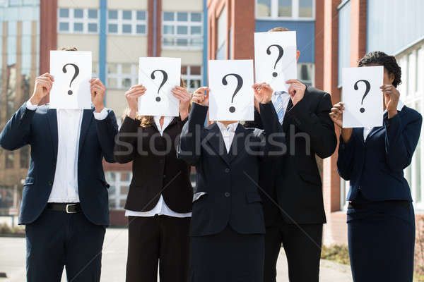 Businesspeople Hiding Face Behind Question Mark Sign Stock photo © AndreyPopov