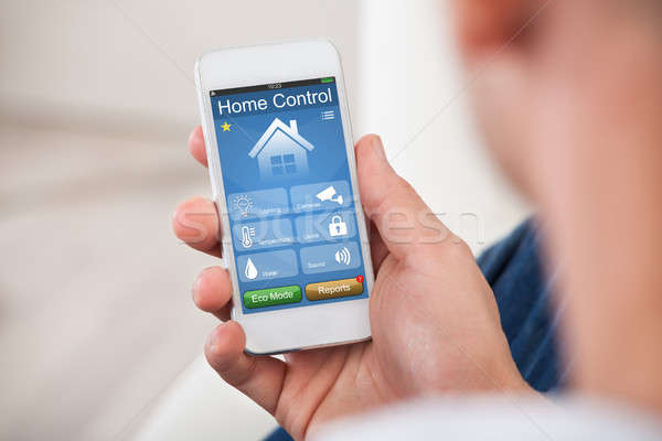 Person Using Home Control System On Mobilephone Stock photo © AndreyPopov