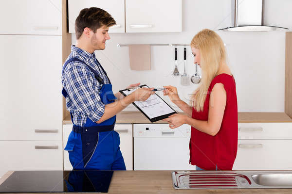 Male Plumber Showing Woman To Sign The Invoice Stock photo © AndreyPopov