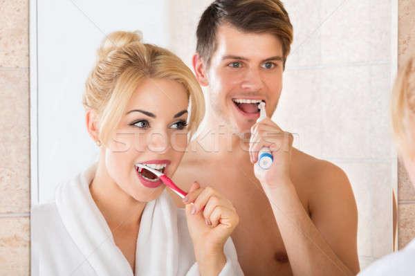 Fiatal pér fogmosás fürdőszoba fiatal mosolyog pár Stock fotó © AndreyPopov