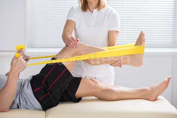 Physiotherapist Giving Treatment With Exercise Band Stock photo © AndreyPopov