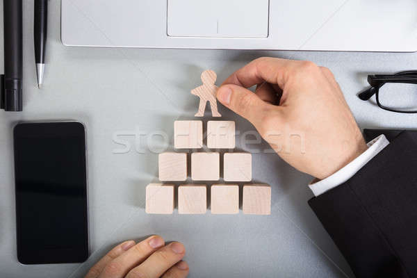 Businessperson Arranging Human Figure Cut Out On Wooden Blocks Stock photo © AndreyPopov