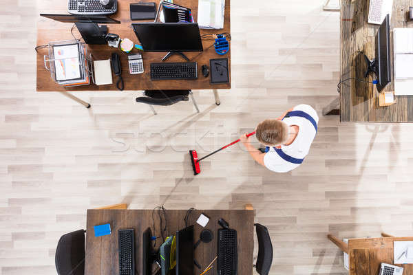 Janitor Cleaning Floor With Broom In Office Stock photo © AndreyPopov