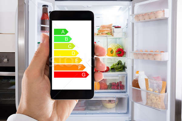 Hand Using Energy Label On Mobile Phone Against Refrigerator Stock photo © AndreyPopov