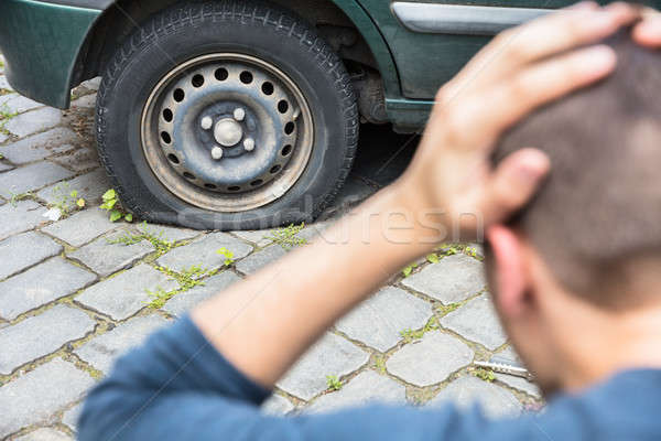 Worried Man Looking At Punctured Car Tire Stock photo © AndreyPopov