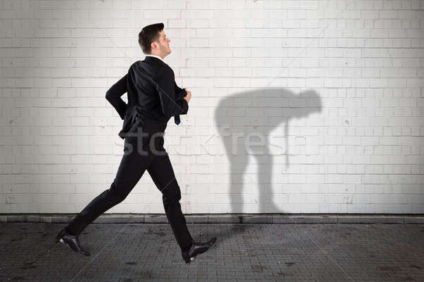 Businessman Running On Sidewalk With His Shadow On Wall Stock photo © AndreyPopov