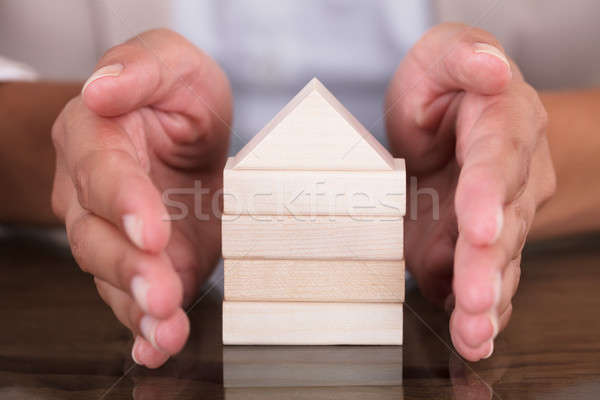 Hand Covering Model Home Made From Wooden Blocks Stock photo © AndreyPopov