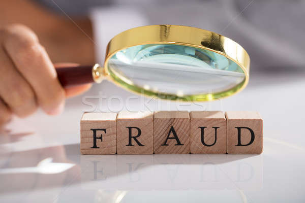 Person Examining Fraud Blocks Through Magnifying Glass Stock photo © AndreyPopov