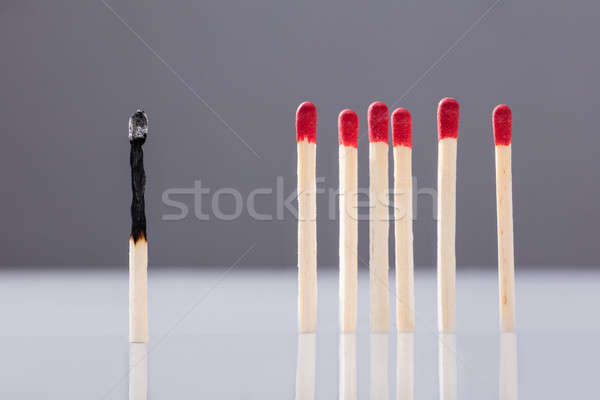 Burnt Matchstick Separated By Red Matchsticks Stock photo © AndreyPopov