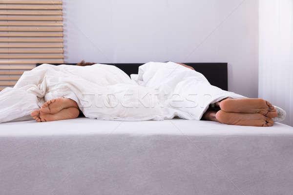 Couple's Feet Sleeping In Bed Stock photo © AndreyPopov