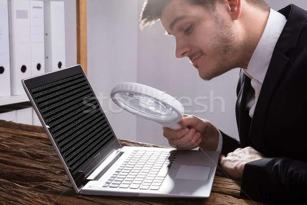Empresario mirando código binario lupa jóvenes Foto stock © AndreyPopov