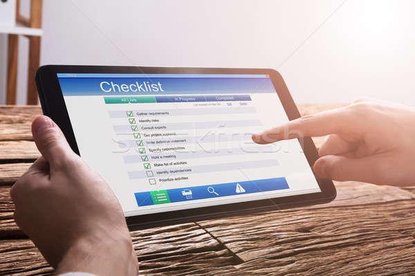 Businessperson Filling Checklist Form On Digital Tablet Stock photo © AndreyPopov