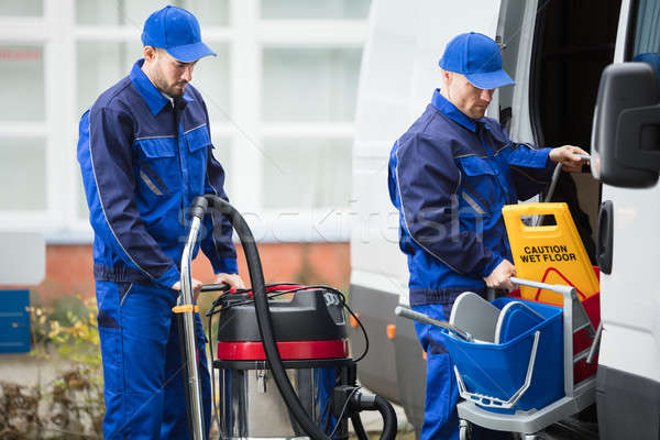 Two Male Janitor Unloading Cleaning Equipment From Vehicle Stock photo © AndreyPopov