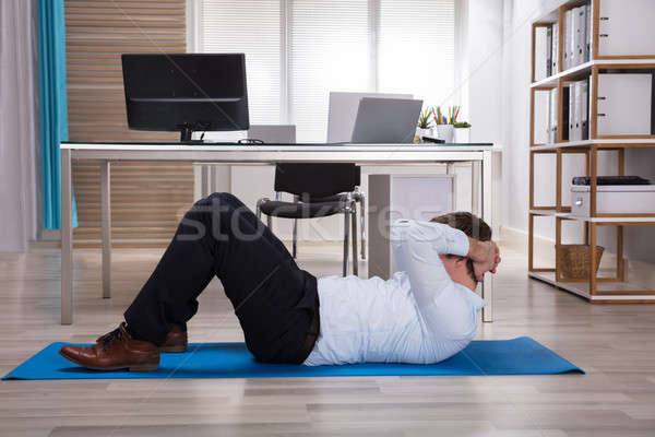 Businessman Doing Exercise On Exercise Mat Stock photo © AndreyPopov