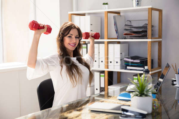 Stock photo: Businesswoman Exercising With Dumbbells