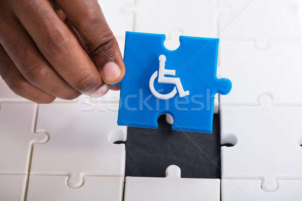 Hand Holding Disabled Wheelchair Icon On Jigsaw Puzzle Stock photo © AndreyPopov