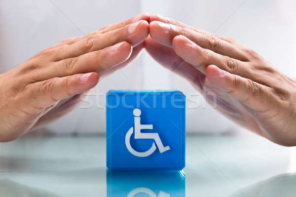 Human hand protecting cubic block with handicap icon Stock photo © AndreyPopov