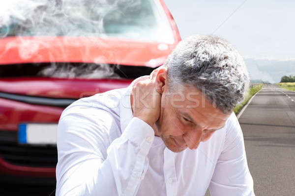 Stock photo: Man Suffering From Neck Pain In Front Of Breakdown Car