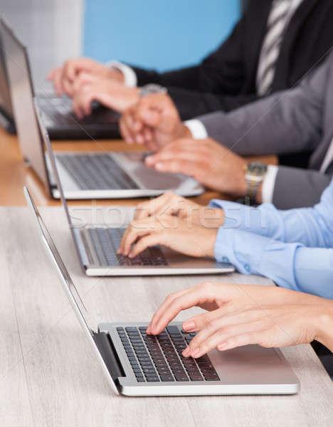 Közelkép üzletemberek laptopot használ csetepaté asztal nő Stock fotó © AndreyPopov