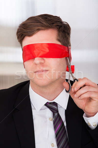 Businessman cutting his blindfold Stock photo © AndreyPopov