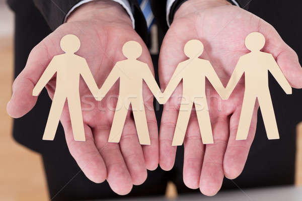Male Hand Holding Human Figure Cutout Stock photo © AndreyPopov
