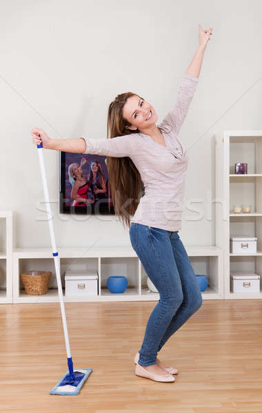 Stock photo: Young Woman Dancing While Cleaning Floor