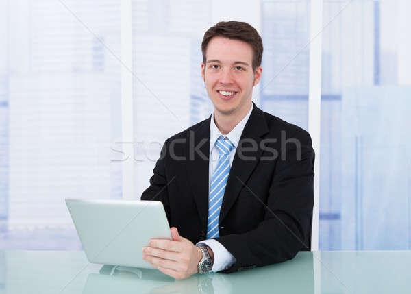 Confident Businessman Using Digital Tablet At Desk Stock photo © AndreyPopov