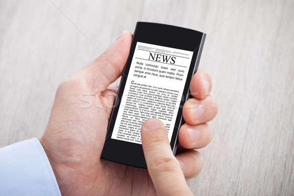 рук серфинга Новости смартфон столе Сток-фото © AndreyPopov