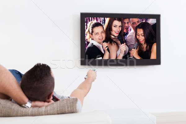 Adam dinleme karaoke tv genç oturma odası Stok fotoğraf © AndreyPopov